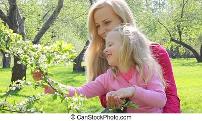 girl plays with branch of the aple trees