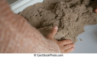 Girl plays with sand and dinosaurs on kinetic sand -...