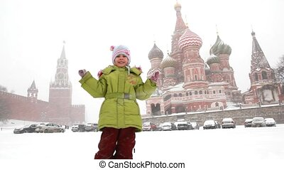 5-6 years old girl plays with snowballs near Moscow Kremlin under snowfall