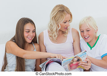 Girl pointing at a magazine in her mother hands