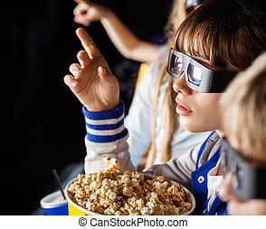 Girl Pointing While Watching 3D Movie With Siblings