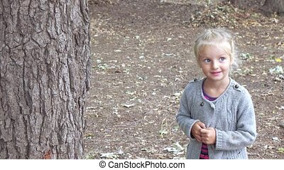 Girl pokes stick hollow - On the pine needles the little...