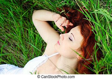 Girl portrait, lying in grass field.