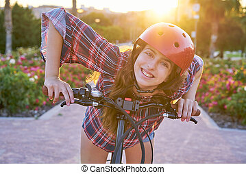 Girl portrait on bicycle with helmet smiling