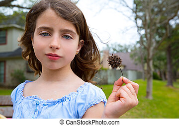 girl portrait with sweetgum spiked fruit on park