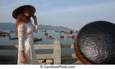 girl poses in vietnamese hat on embankment