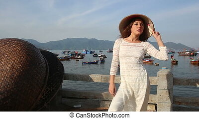 girl poses in vietnamese hat on embankment