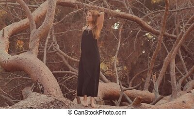 Girl posing at sunset standing on pine trunk