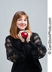 Girl posing in front of the camera with an apple in her hands