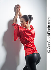 girl posing in red silk tunic and black leggings