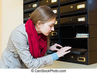 Girl posing near empty mailbox
