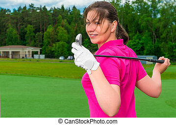 girl posing on the field with a golf a club
