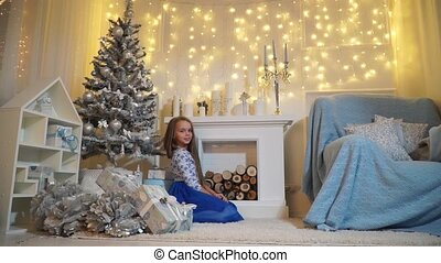 Girl posing sitting on the floor near the fireplace near the Christmas tree