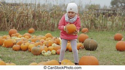 Girl posing with bright pumpkin in yard - Portrait of little...