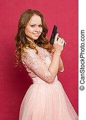 girl posing with gun in his hand and looks - Girl posing...