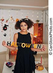 Girl posing with Halloween inscription