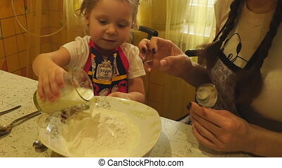 Girl pouring in a bowl of milk for the dough