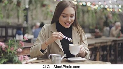 Girl pouring sugar in coffee - Stylish young female sitting...