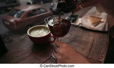 Girl pours cold brew coffee in a glass of ice in a cafe in the evening.