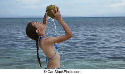 girl pours on herself coconut juice