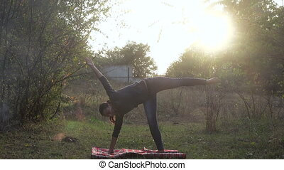 Girl practices yoga in nature