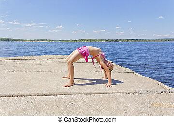 Girl practices yoga  in pose footbridge