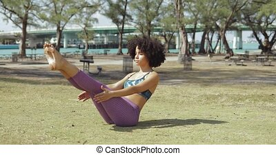 Girl practicing abdomen muscles on meadow - Confident black...
