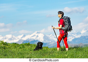 Girl practicing trekking in the mountains with his sheepdog