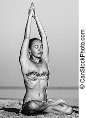 Girl practicing yoga on the beach at sunset. Lotus Pose. black and white photo