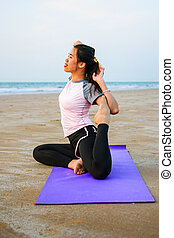 Girl practicing yoga on the beach at sunset