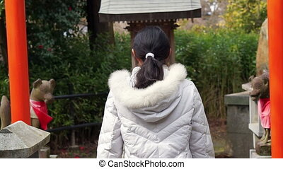 girl praying at Japanese red shrine