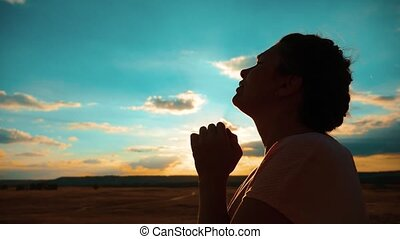 girl praying. girl folded her hands in prayer silhouette at sunset. slow motion video. Girl folded her hands in prayer lifestyle pray to God. asks forgiveness for sins of repentance. believing girl. concept Christianity religion catholicism