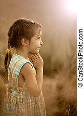 Girl prays in evening wheat field