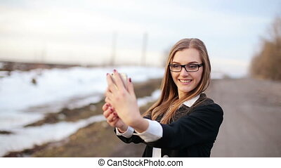 girl preens doing selfie using front facing camera of the smartphone