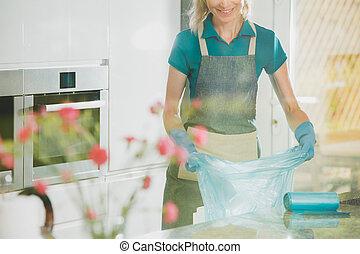 Girl prepares garbage bags - Blonde girl prepares garbage...