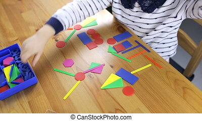 Girl preschooler performs a task with geometric shapes