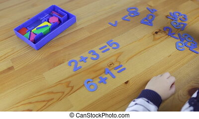 Girl preschooler studying arithmetic solves an example