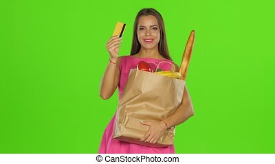 Girl pressed the card and package to himself and smiles. Green screen