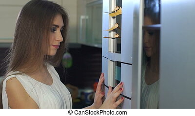 Girl presses the buttons on the touch screen of the modern oven in the kitchen.