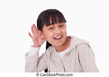 Girl pricking up her ear against a white background