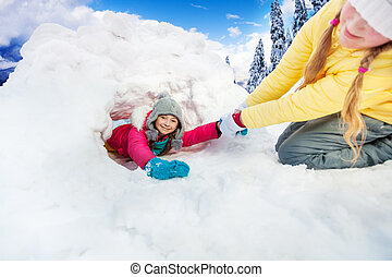 Girl pull on her friend from the snow cave