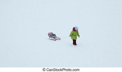 girl pulls empty sled for cord on snow