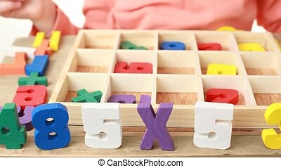 girl pulls out wooden figures numbers of box with cells and puts them on table
