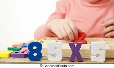 girl pulls out wooden figures of box with cells and puts them on table