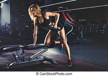 Girl pumping up muscles with dumbbells