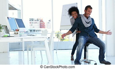 Girl pushing her co worker on a chair