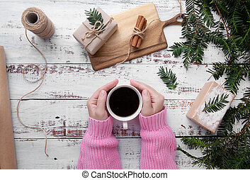 girl puts a cup of coffee on the table with gifts