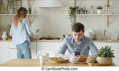 girl puts biscuits cups on table guy looks into phone -...