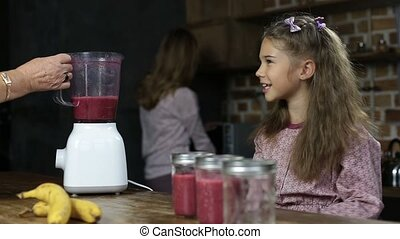 Girl puts drinking straws into jars with smoothie -...