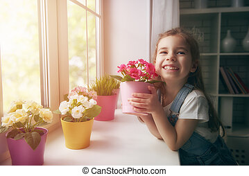 girl puts flowers by window